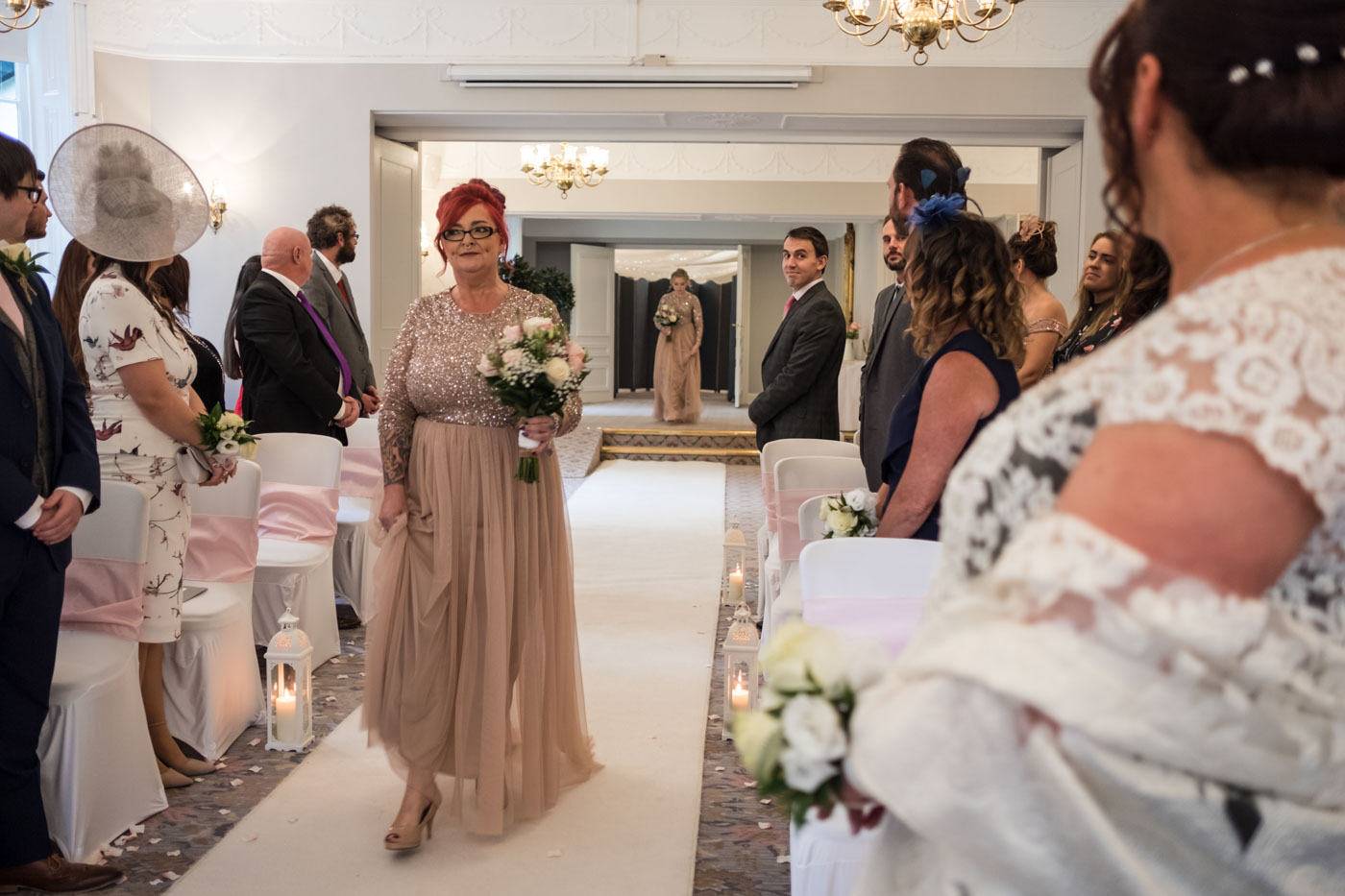 bridesmaid walking down the aisle with pink dress