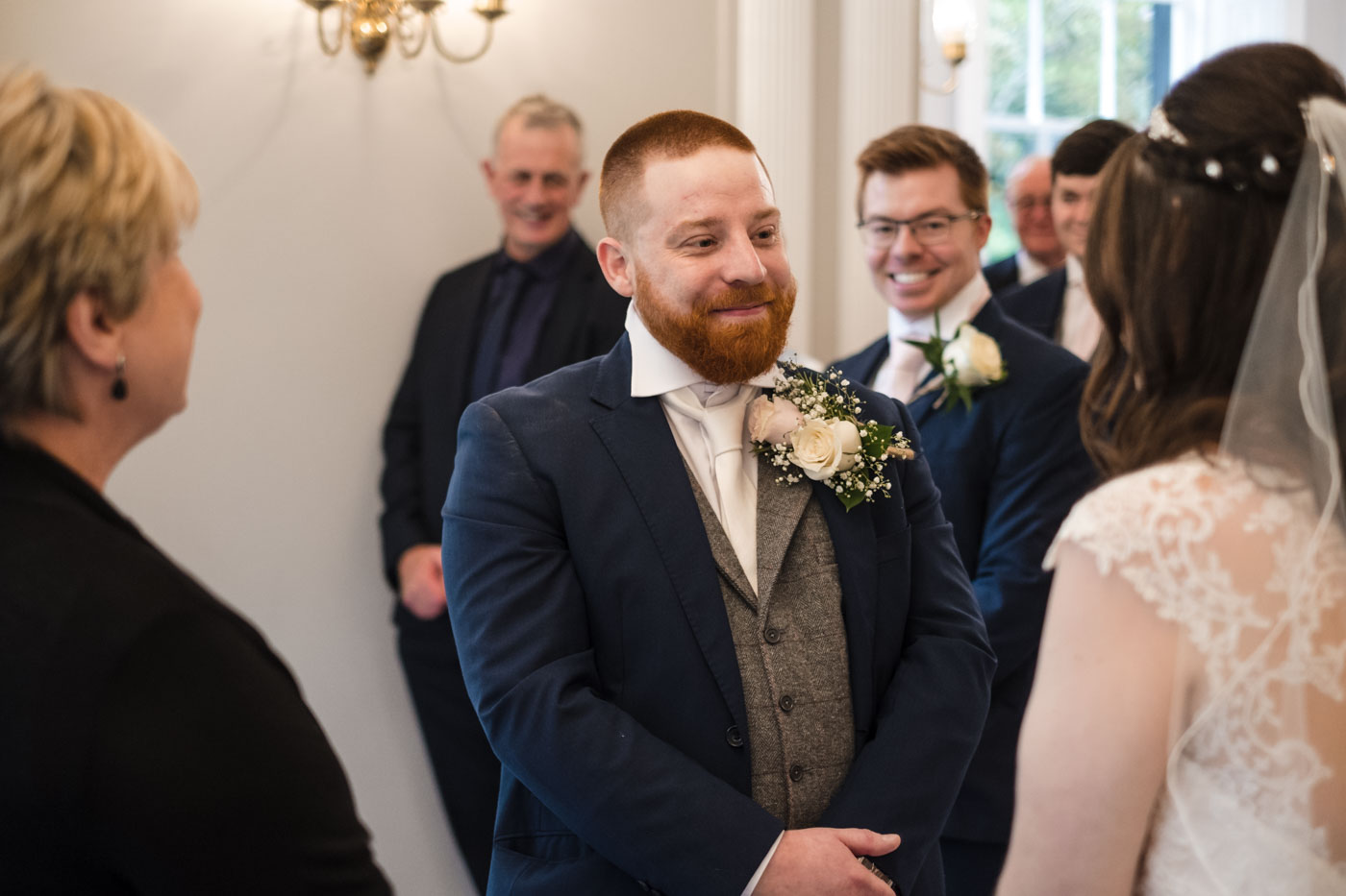 grooms smiling at his wife to be