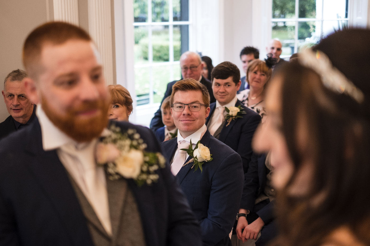 best man looking happy as he watched the wedding ceremony
