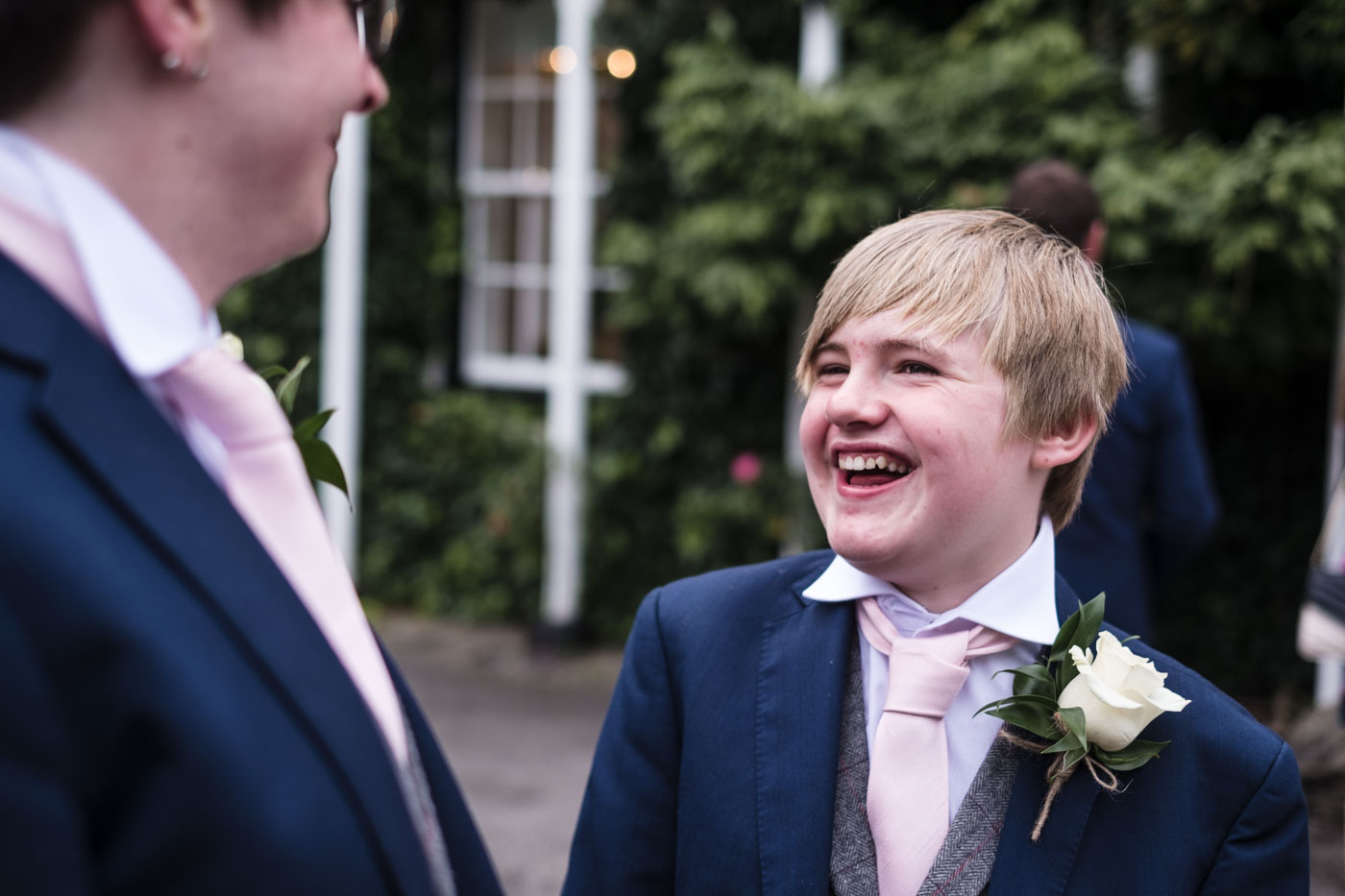 groomsman laughing with green foliage in the background, real moments at a wedding
