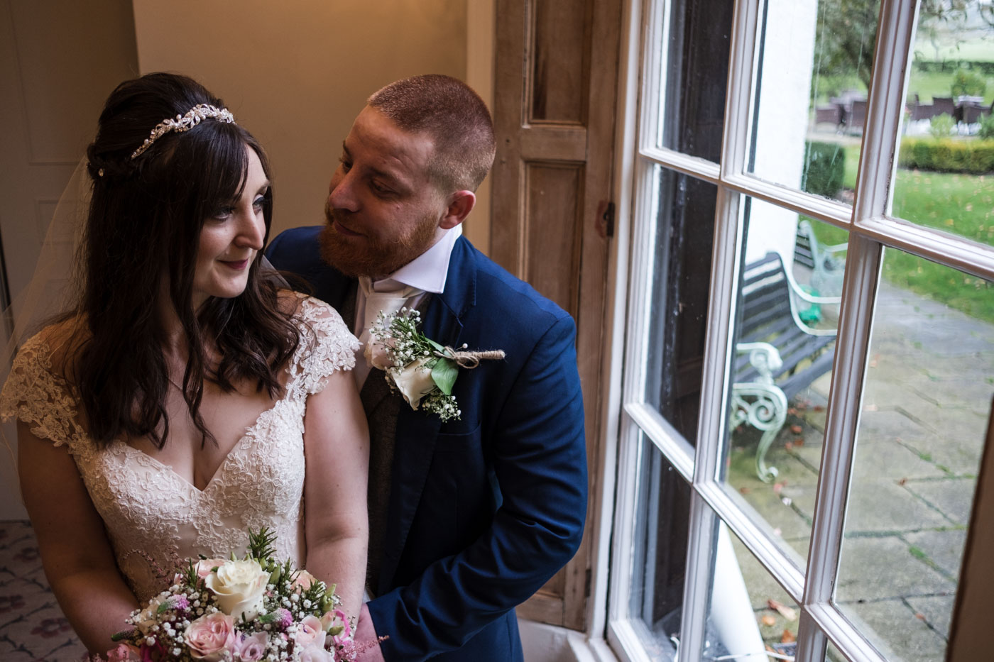 couple in front of window at country house wedding venue, relaxed wedding photographer