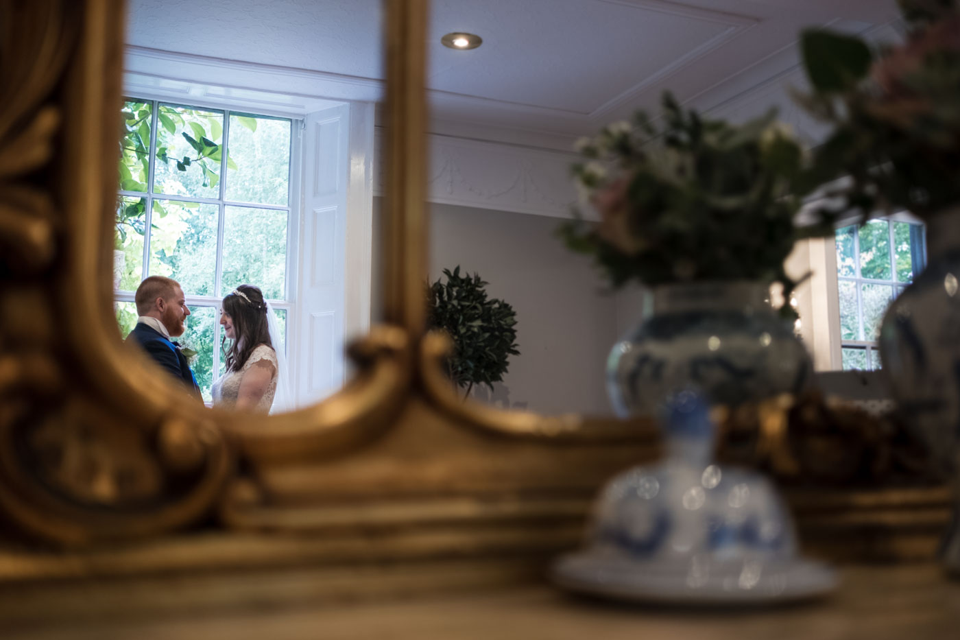 bride and groom reflection in gold mirror