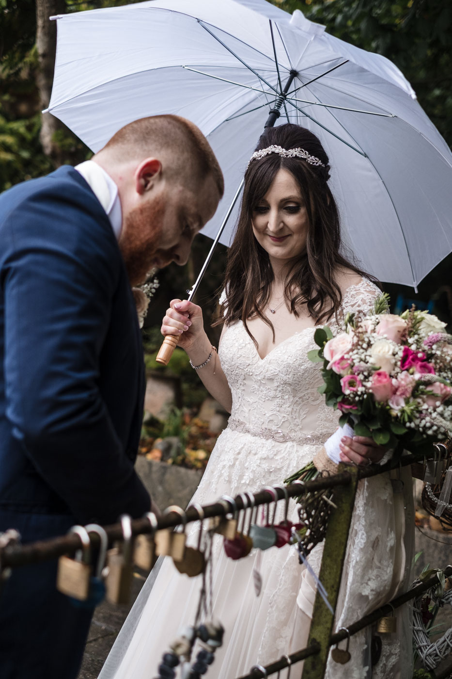 bride and groom putting padlock on the fence at statham lodge