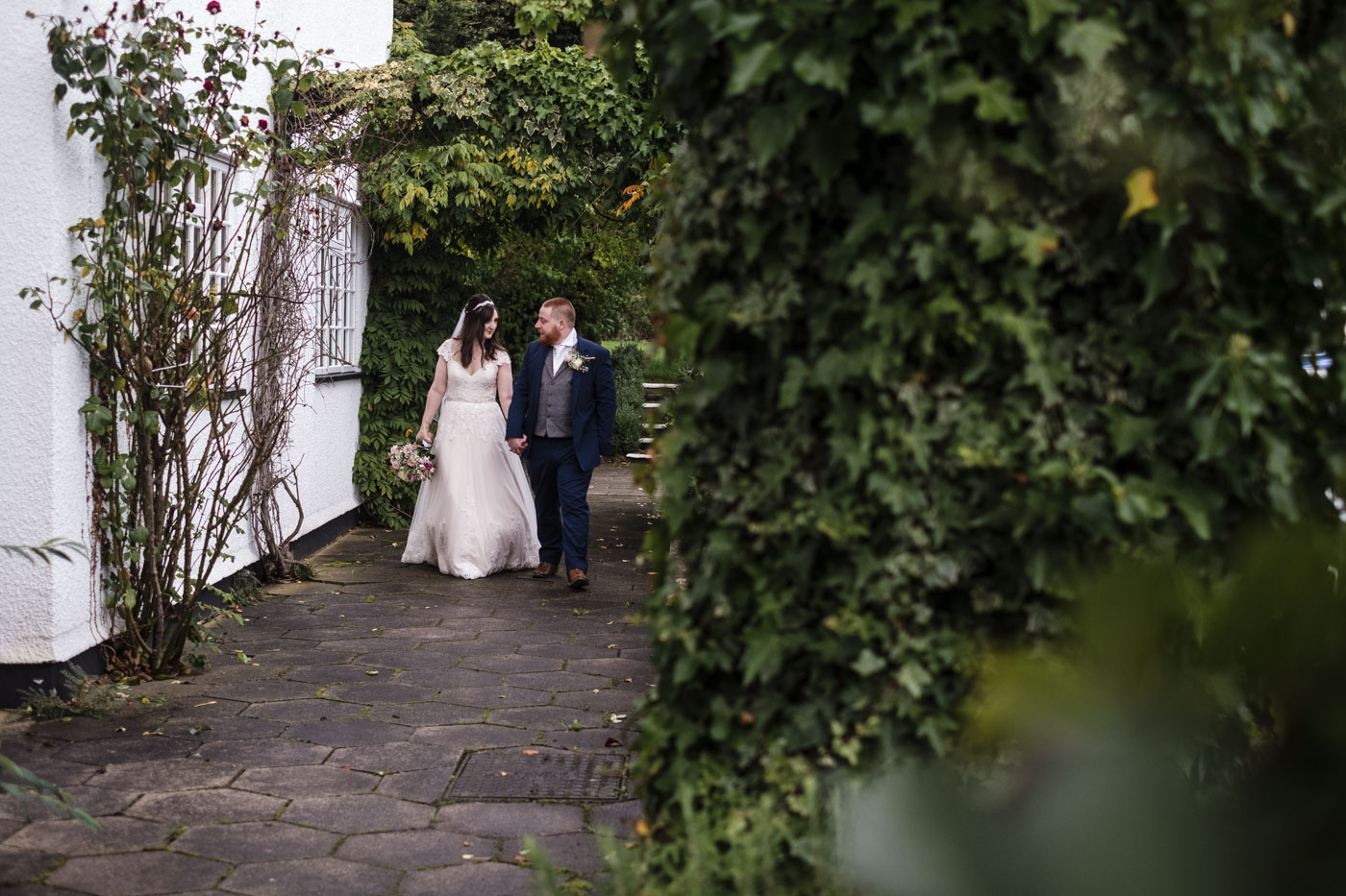 bride and groom looking at each other whilst walking in the hotel gardens