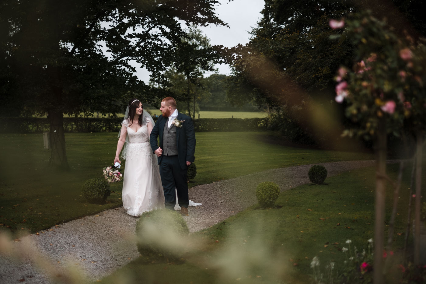 couple portrait with bride and groom walking at statham lodge