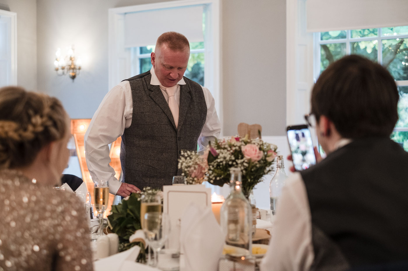 wedding guests being filmed on a mobile phone as he gives speech