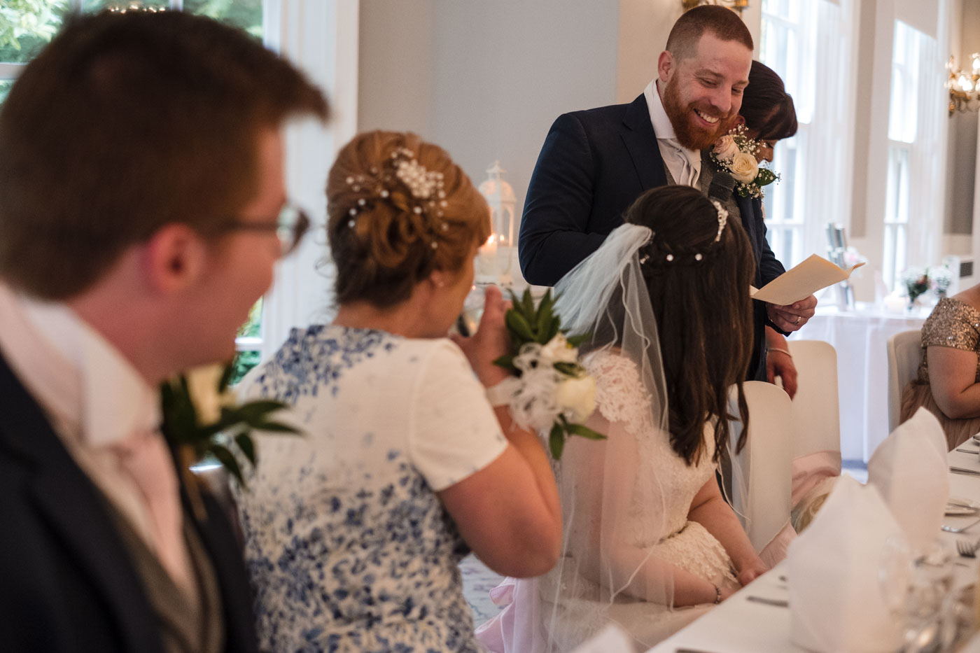 groom laughing looking at his new wife when doing his speech
