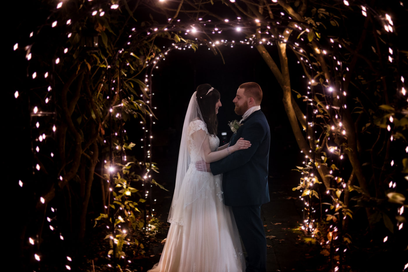 bride and groom portrait with fair lights in the gardens at statham lodge
