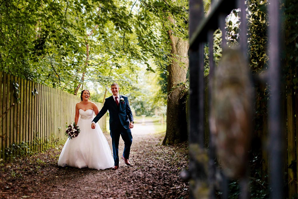 natural photograph of bride and groom walking in the church grounds after the ceremony