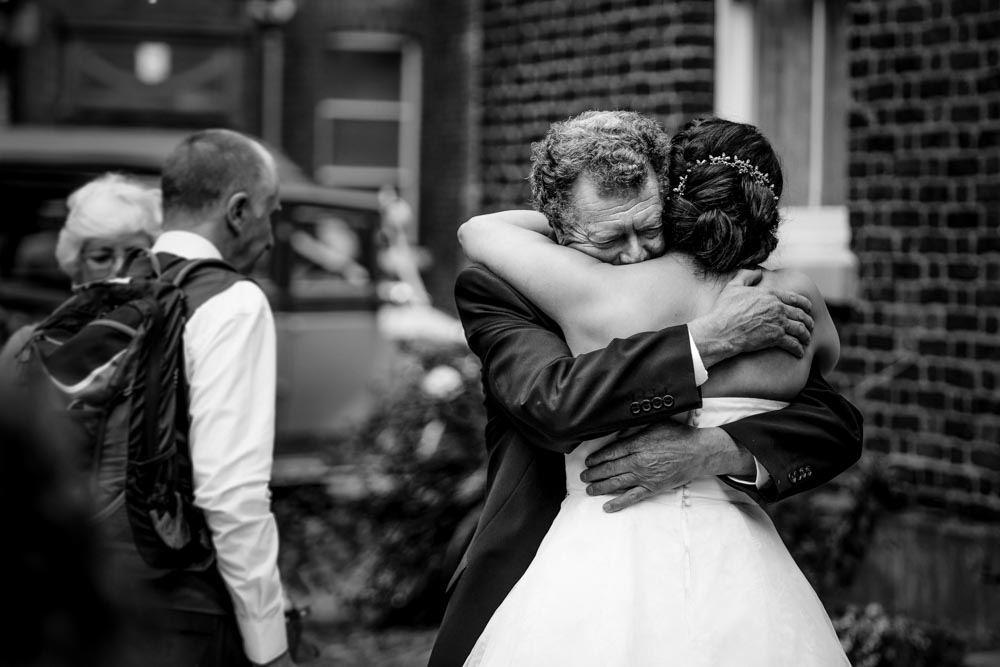 black and white photograph of the bride giving her grandad a big hug after the wedding ceremony