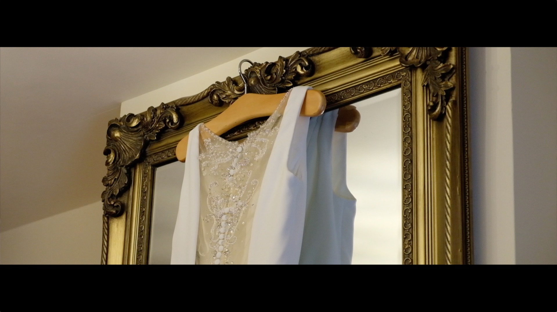 wedding dress hanging on mirror in the barn
