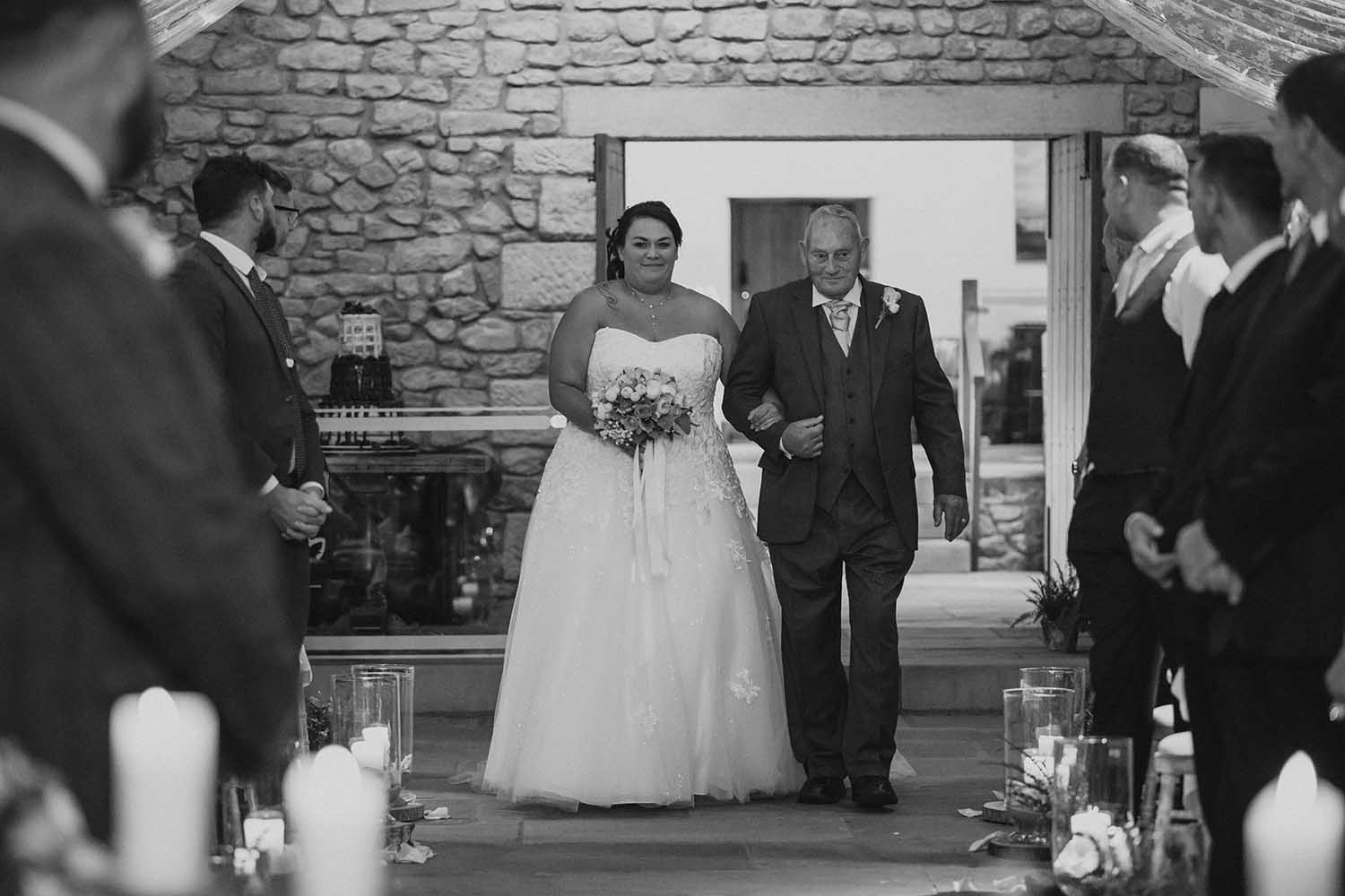 Bride with her dad walking down the aisle at Browsholme Hall tithe Barn