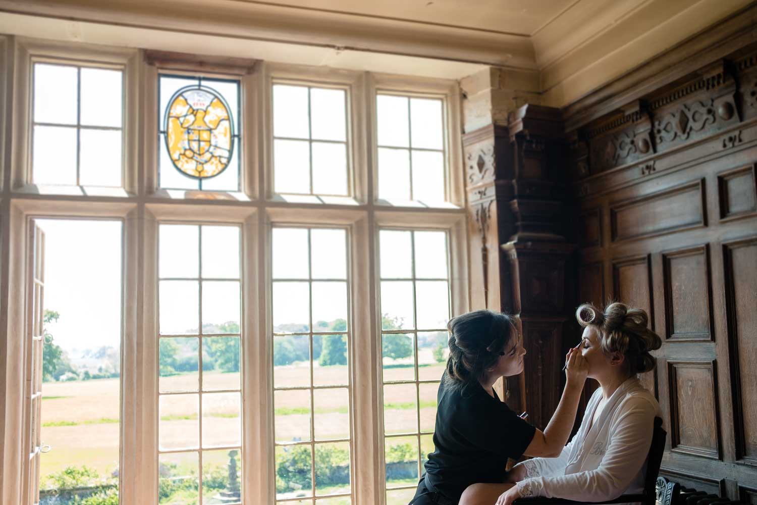 bride having makeup done in front of large window overlooking the south lawn