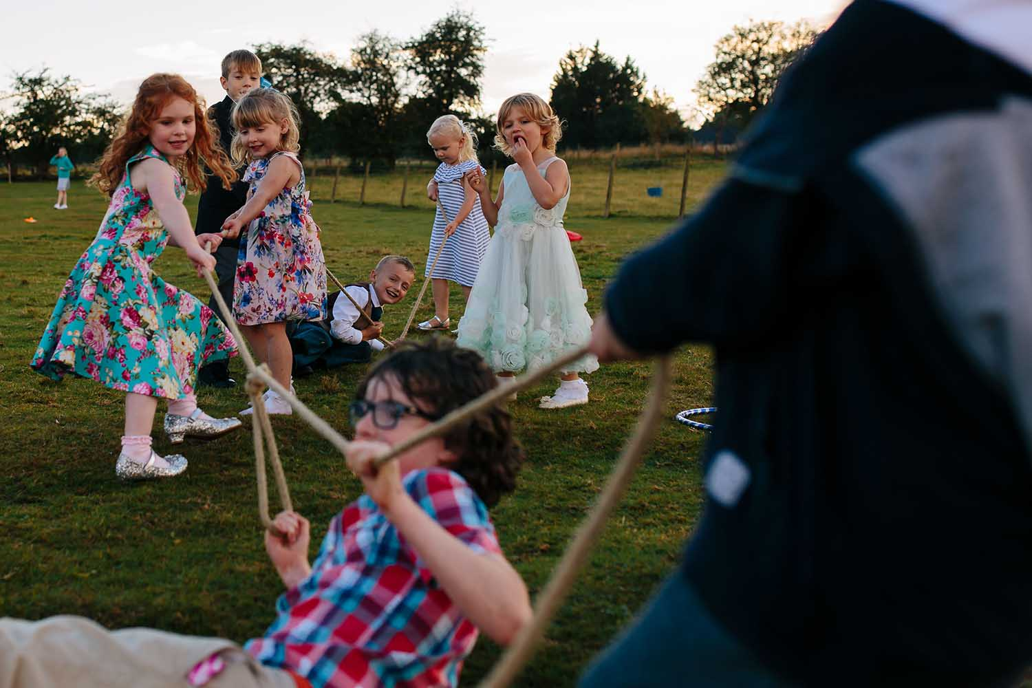 children playing tug of war in outdoor tipi wedding