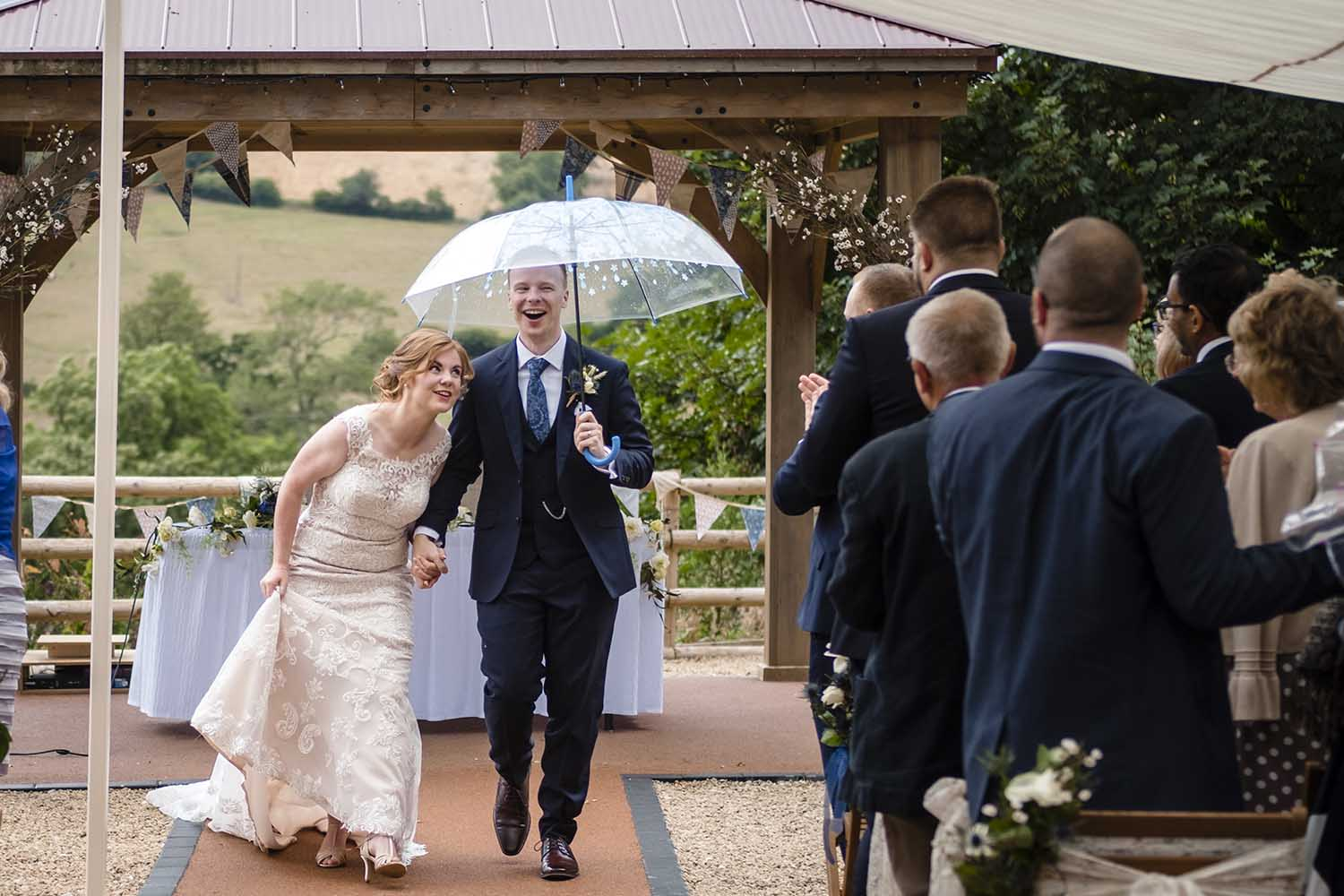 couple with umbrella at outdoor ceremony in the rain