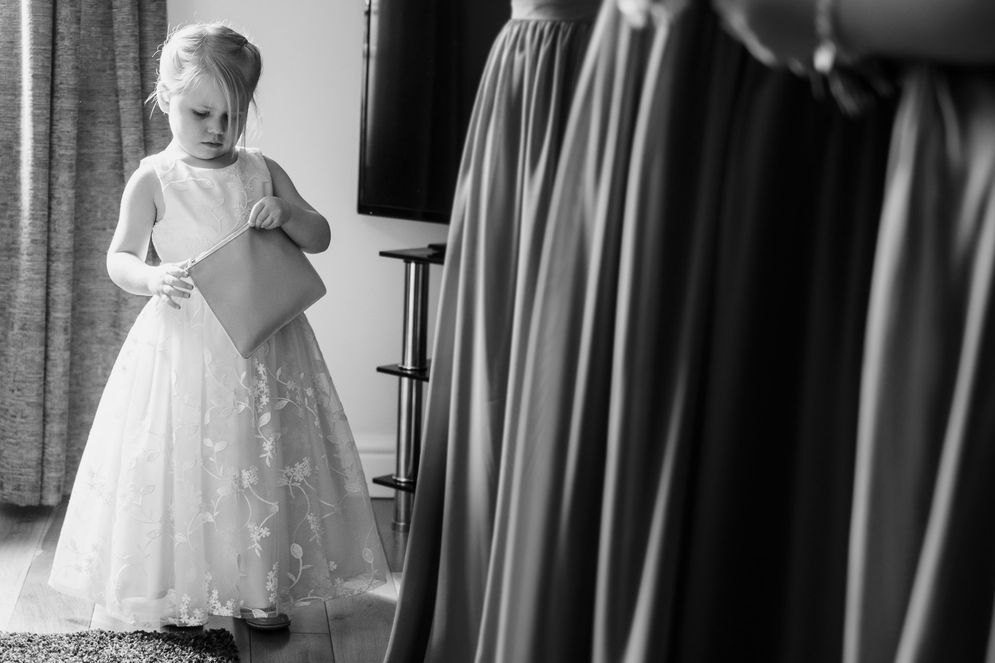 flower girl playing with handbag whilst bridesmaids are getting ready