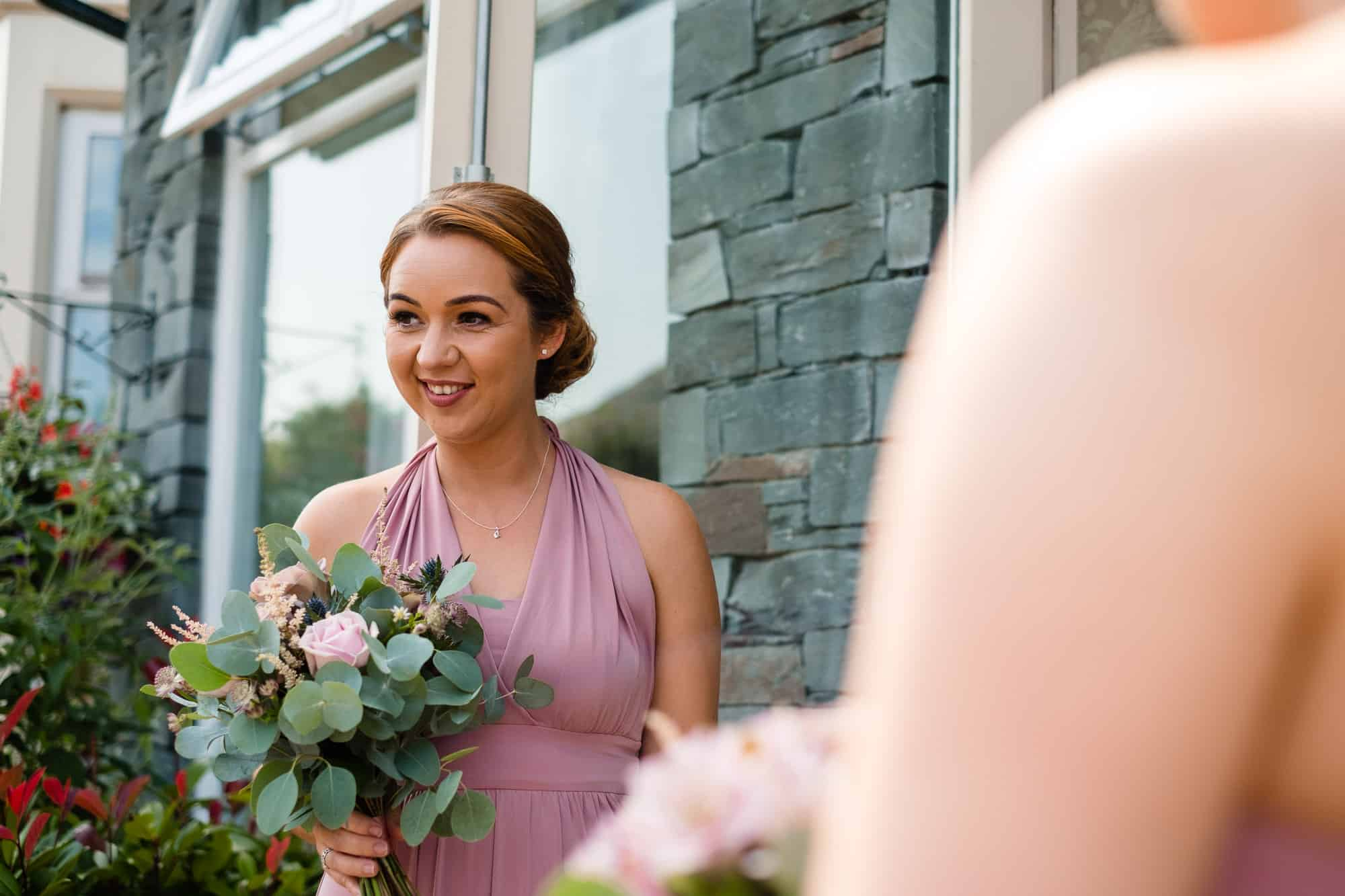 bridesmaid smiling holding bouquet