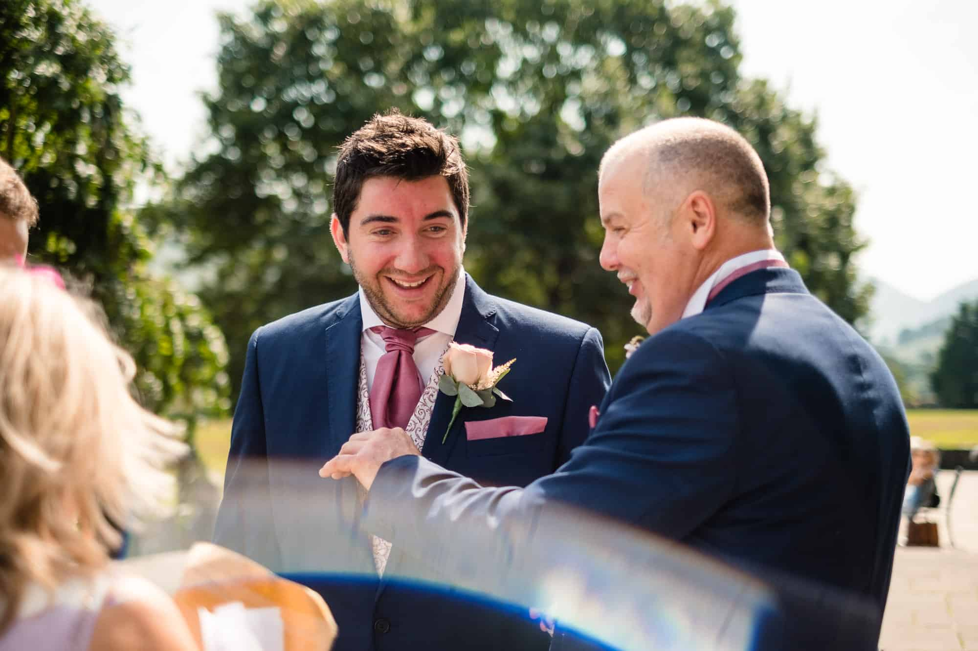 groom with wedding guest in the sun