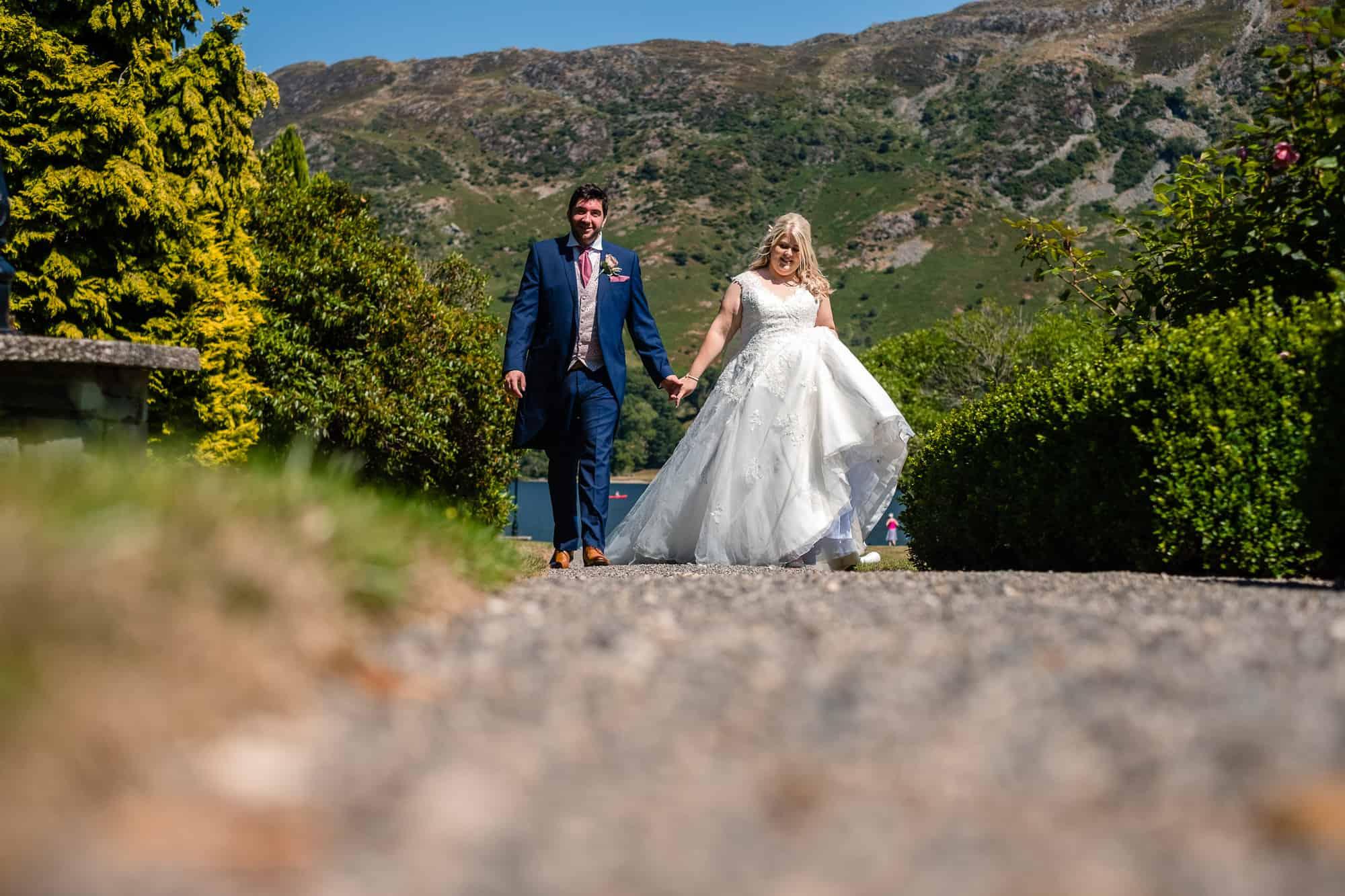 bride and groom walking at inn on the lake wedding venue