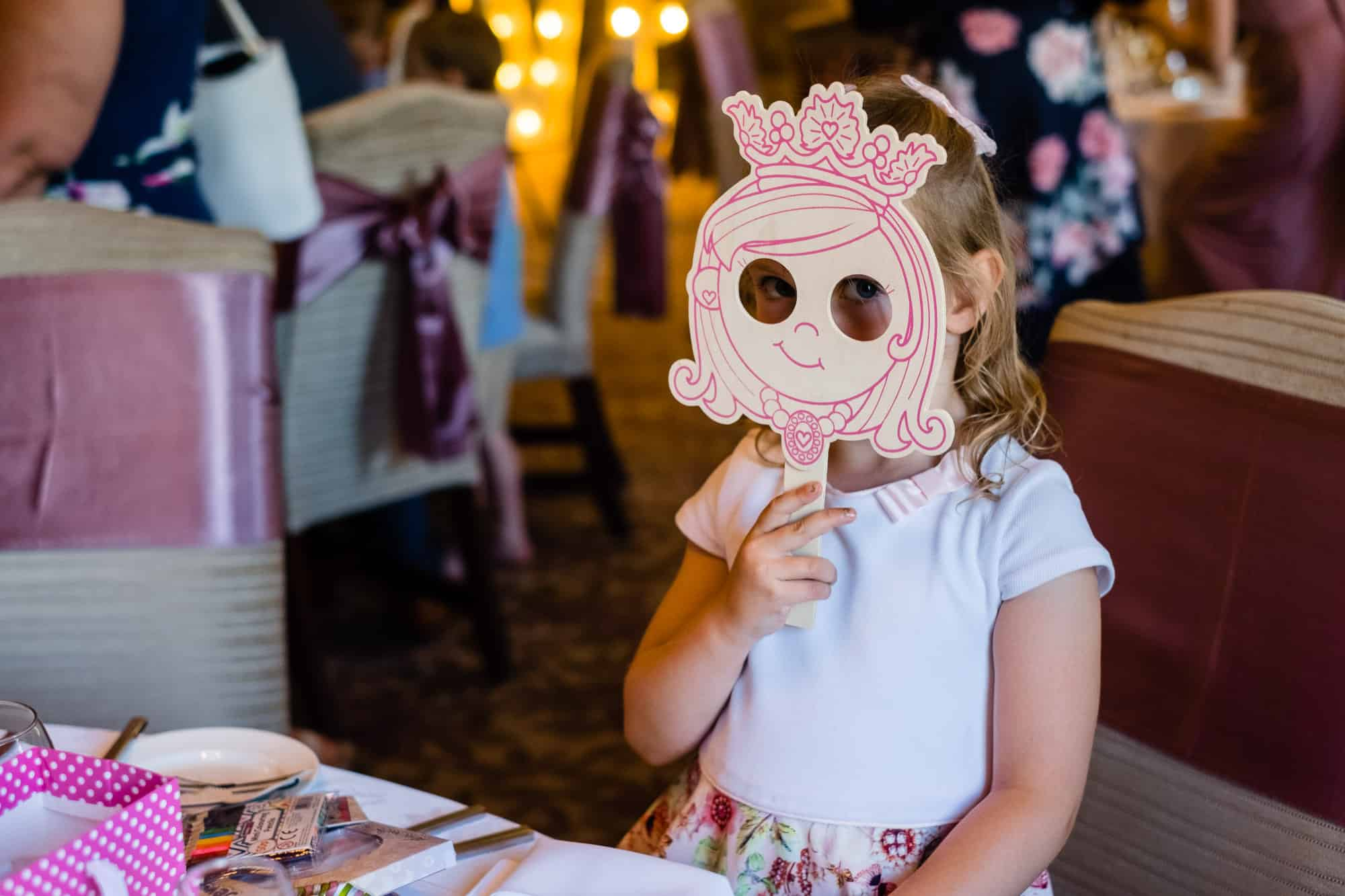 little girl holding up a mask