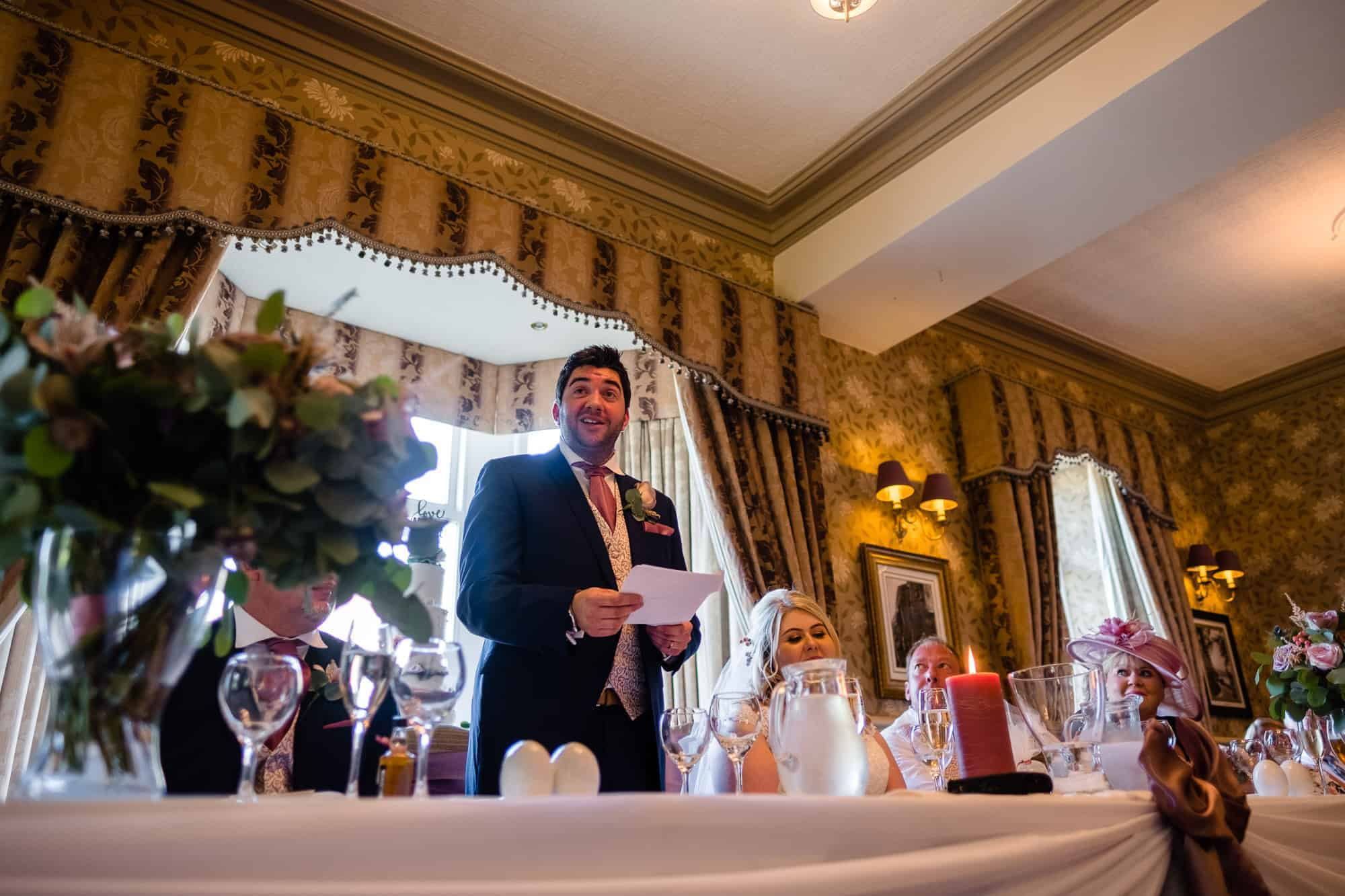 groom giving speech stood up behind the top table