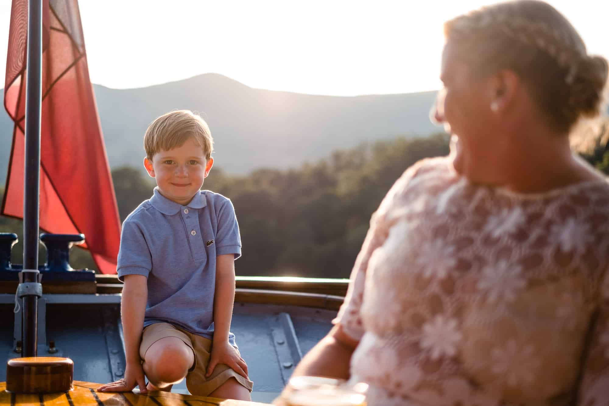 young boy smiling at the back of the boat