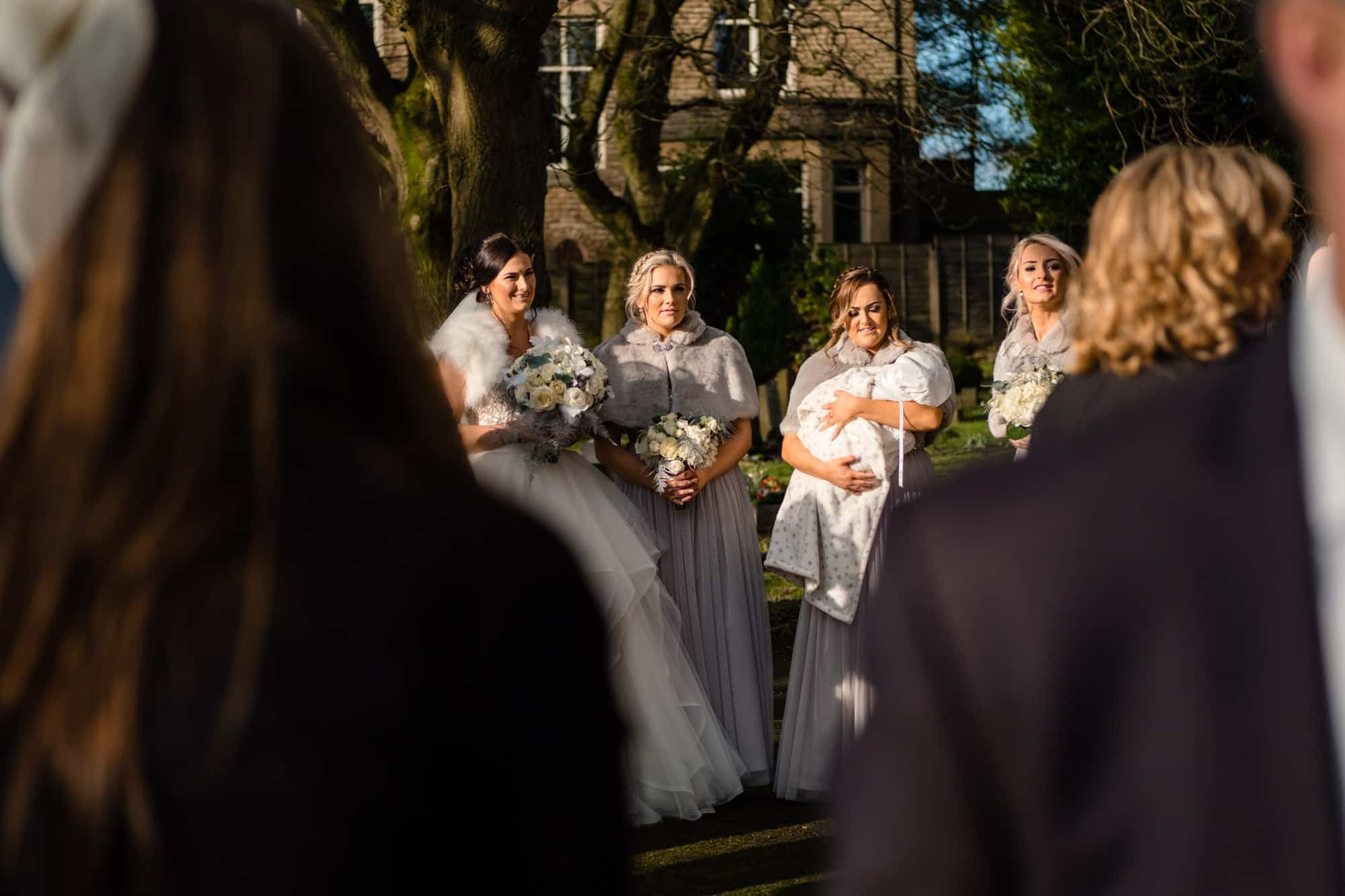 bride with bridesmaids outside church