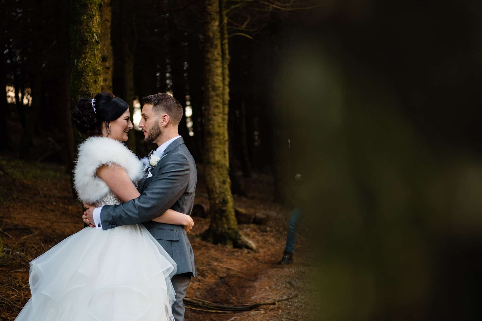 bride and groom cuddling in the woods