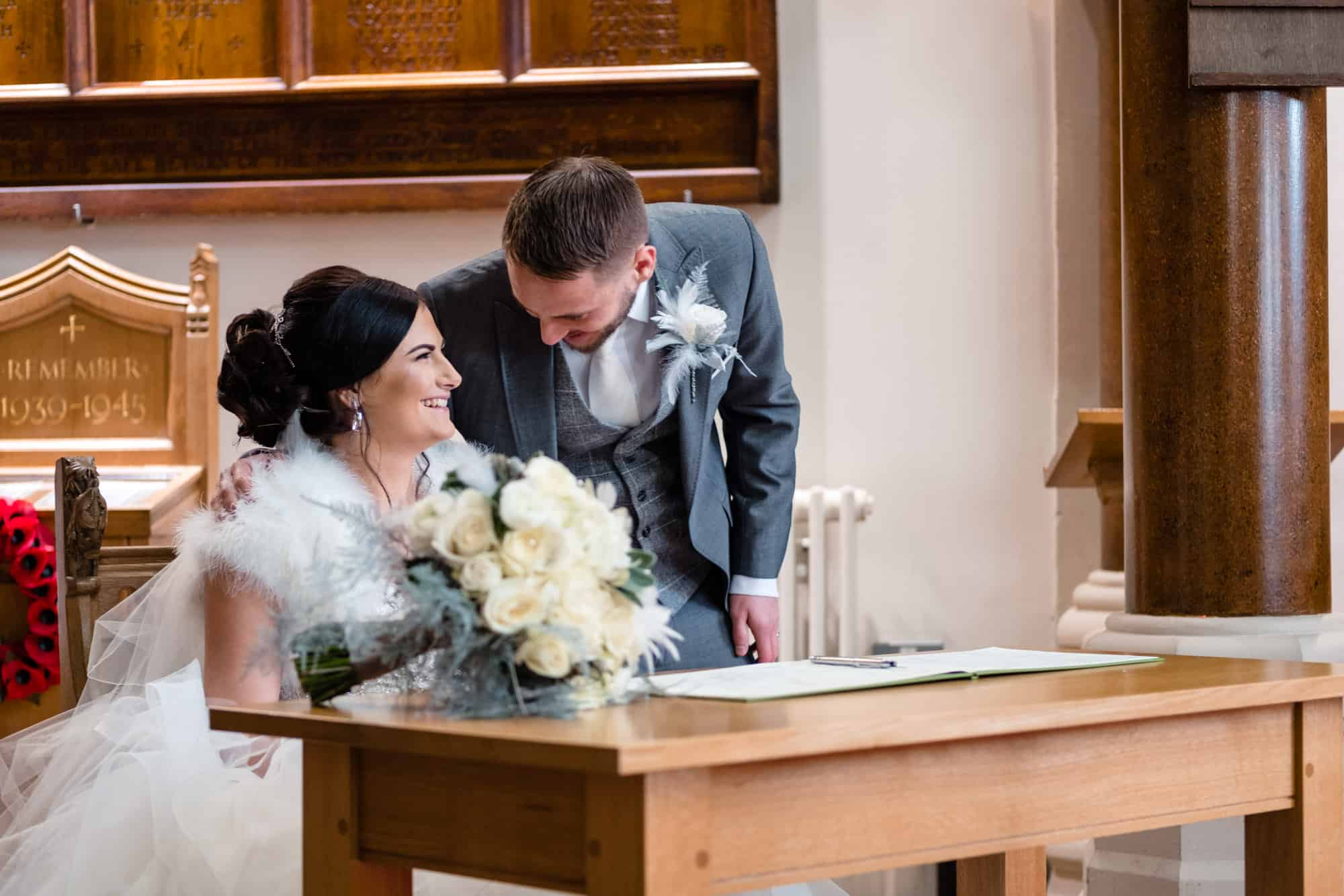 bride and groom laughing as they sign the marriage register