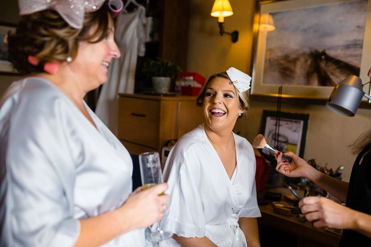bride laughing with mother whilst having make-up done
