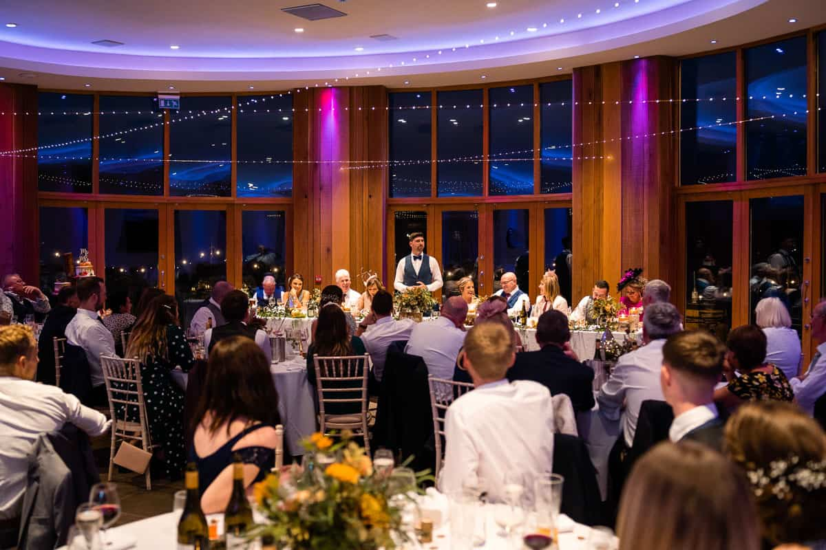 groom doing wedding speech stood behind top table