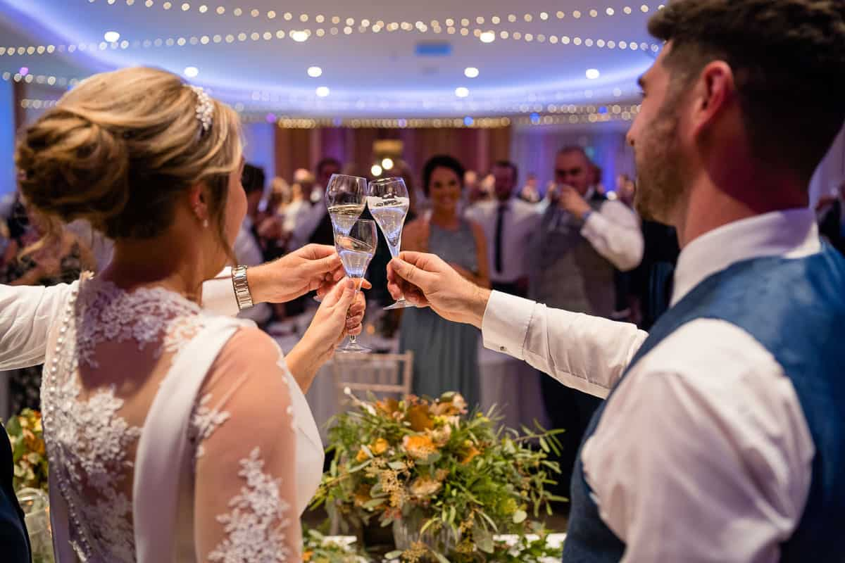 bride and groom making toast with glasses