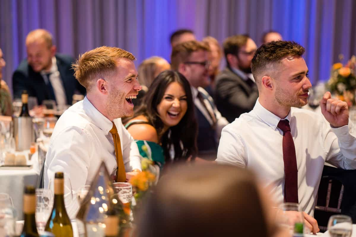 guests laughing at the best mans speech