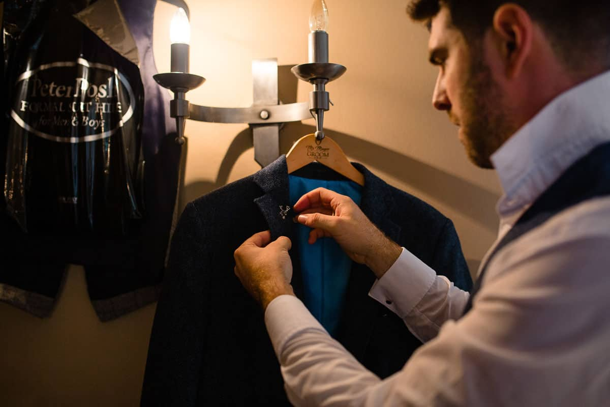 groom putting pin on jacket