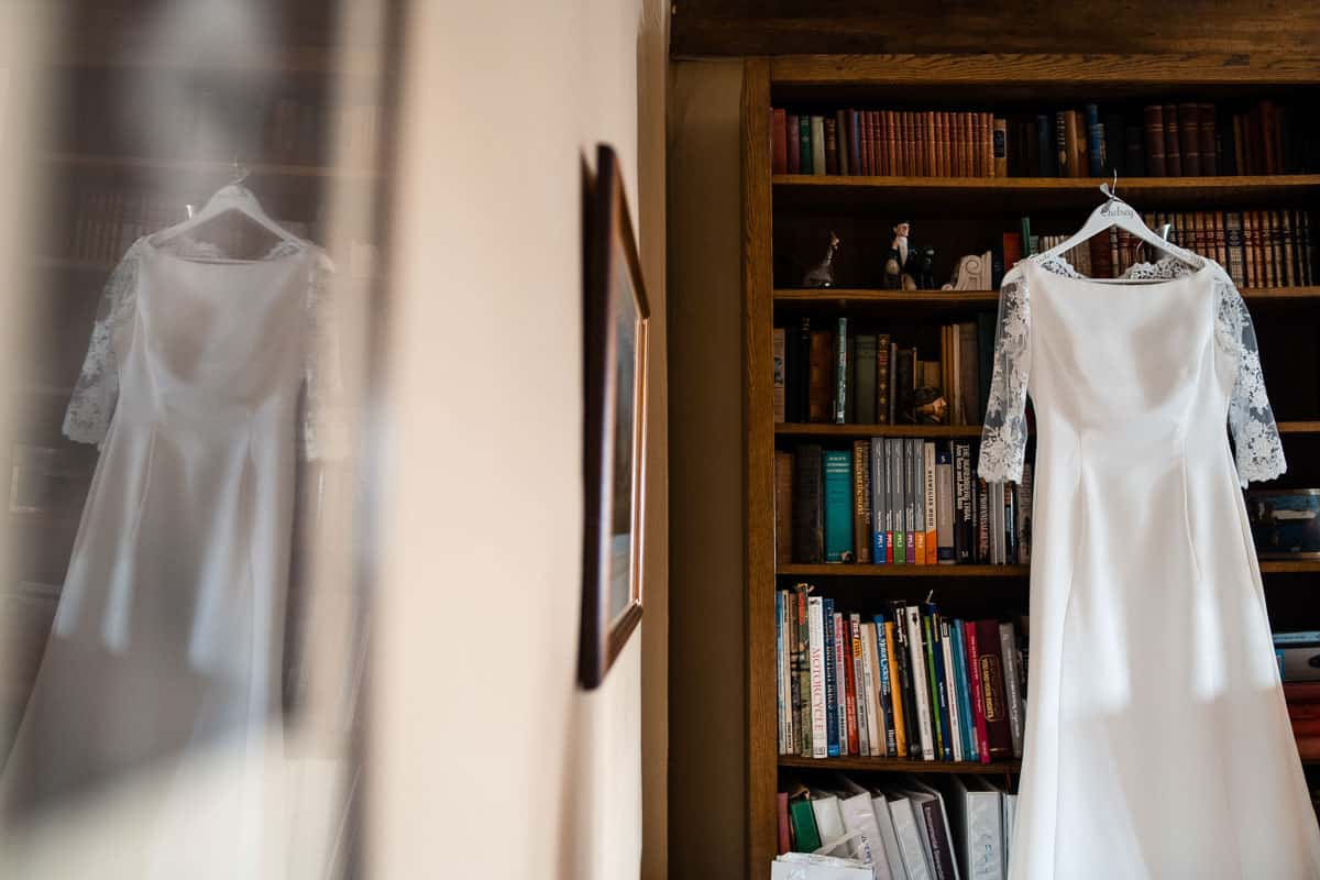 wedding dress hanging on bookcase
