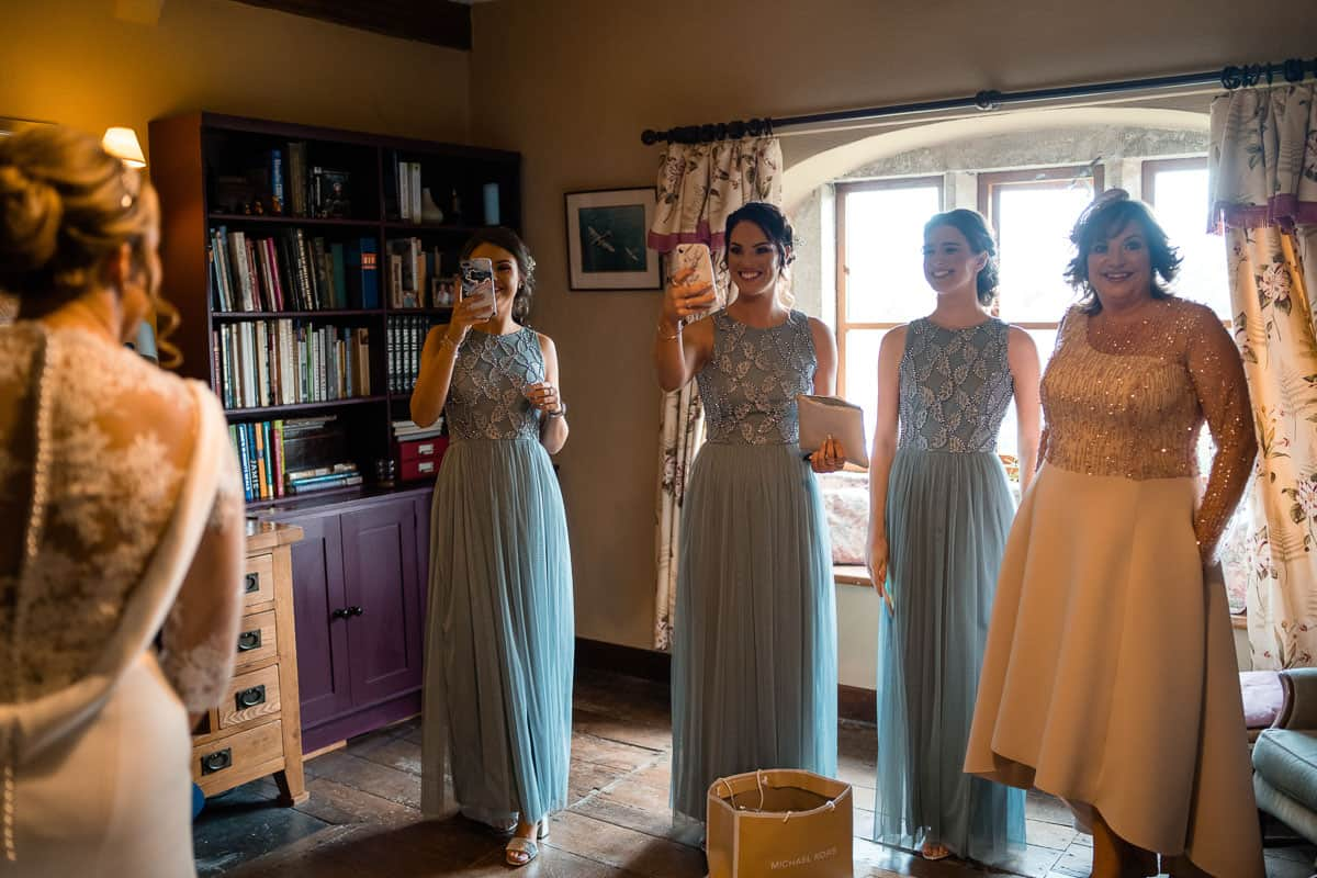 bridesmaids taking photographs on phones of the bride