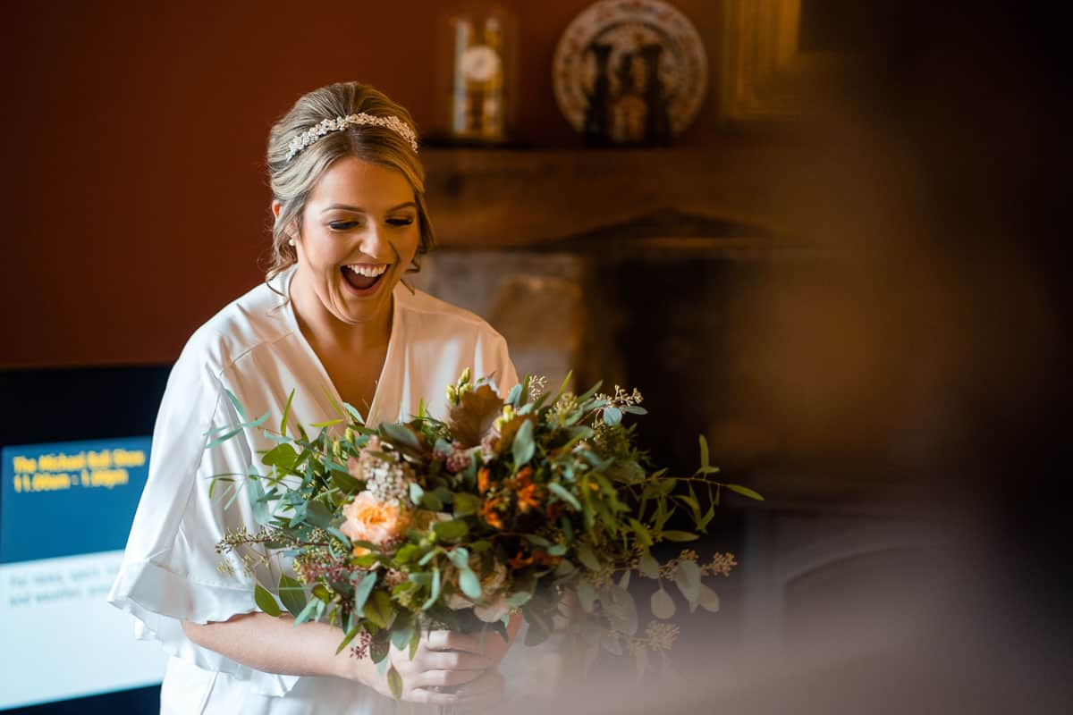 bride smiling as she sees her bouquet for the first time