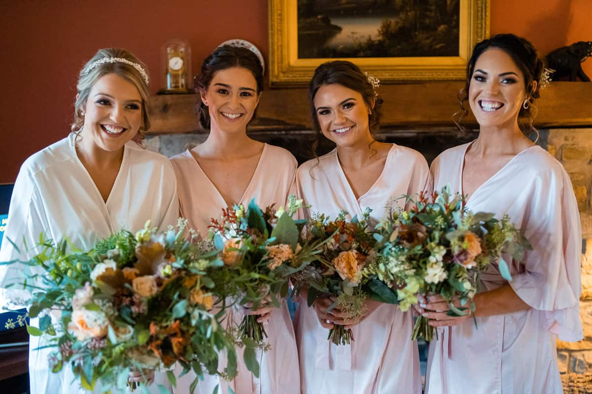 bride and bridesmaids in dressing gowns with bouquets