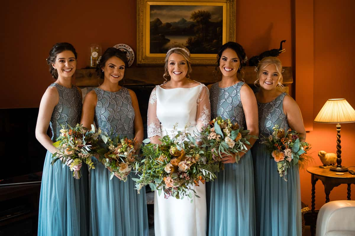 bride and bridesmaids in dresses with bouquets