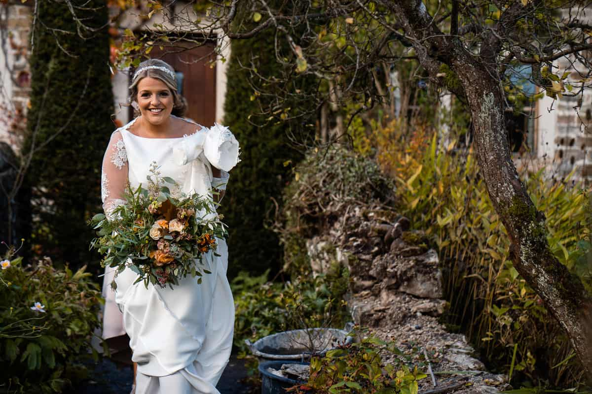 bride walking in the farm house garden on the way to ceremony