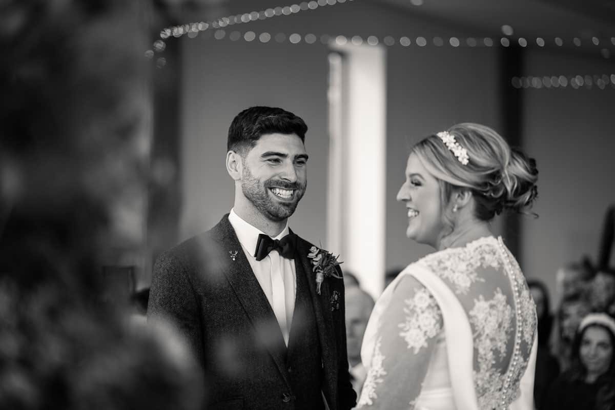 black and white photo of couple smiling during ceremony