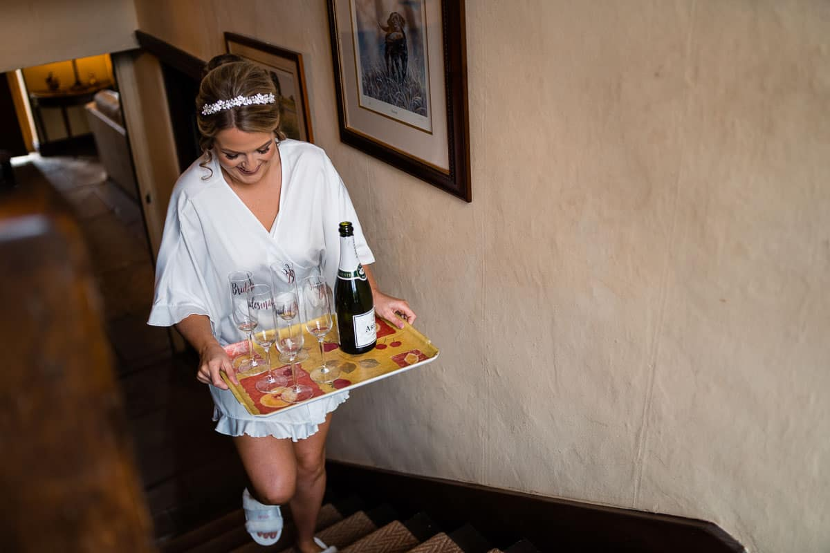 bride carrying tray with Prosecco and glasses up the stairs