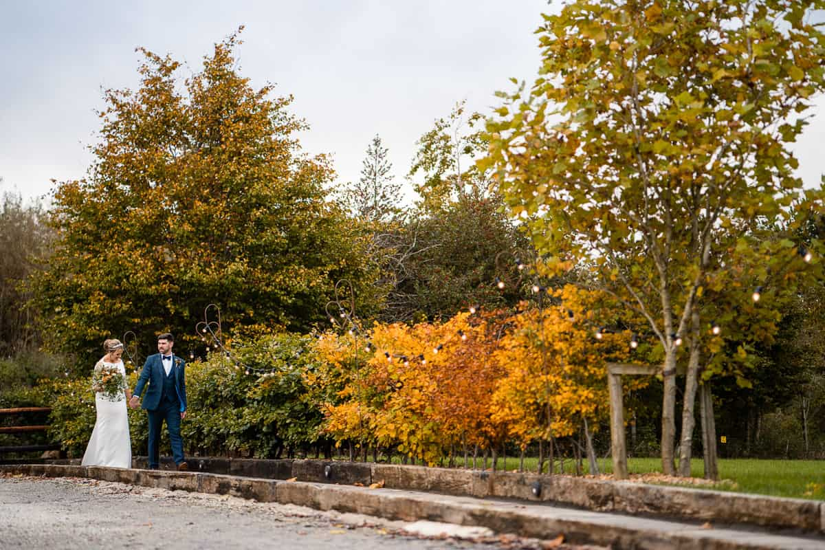 bride and groom walking along the path with autumn colours on the trees