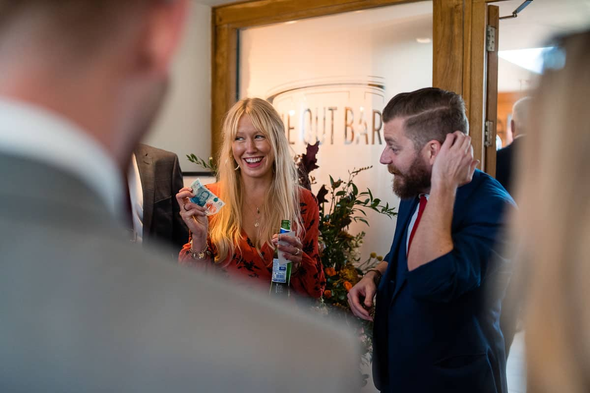 wedding guest with bottle of been in hand laughing at wedding magician