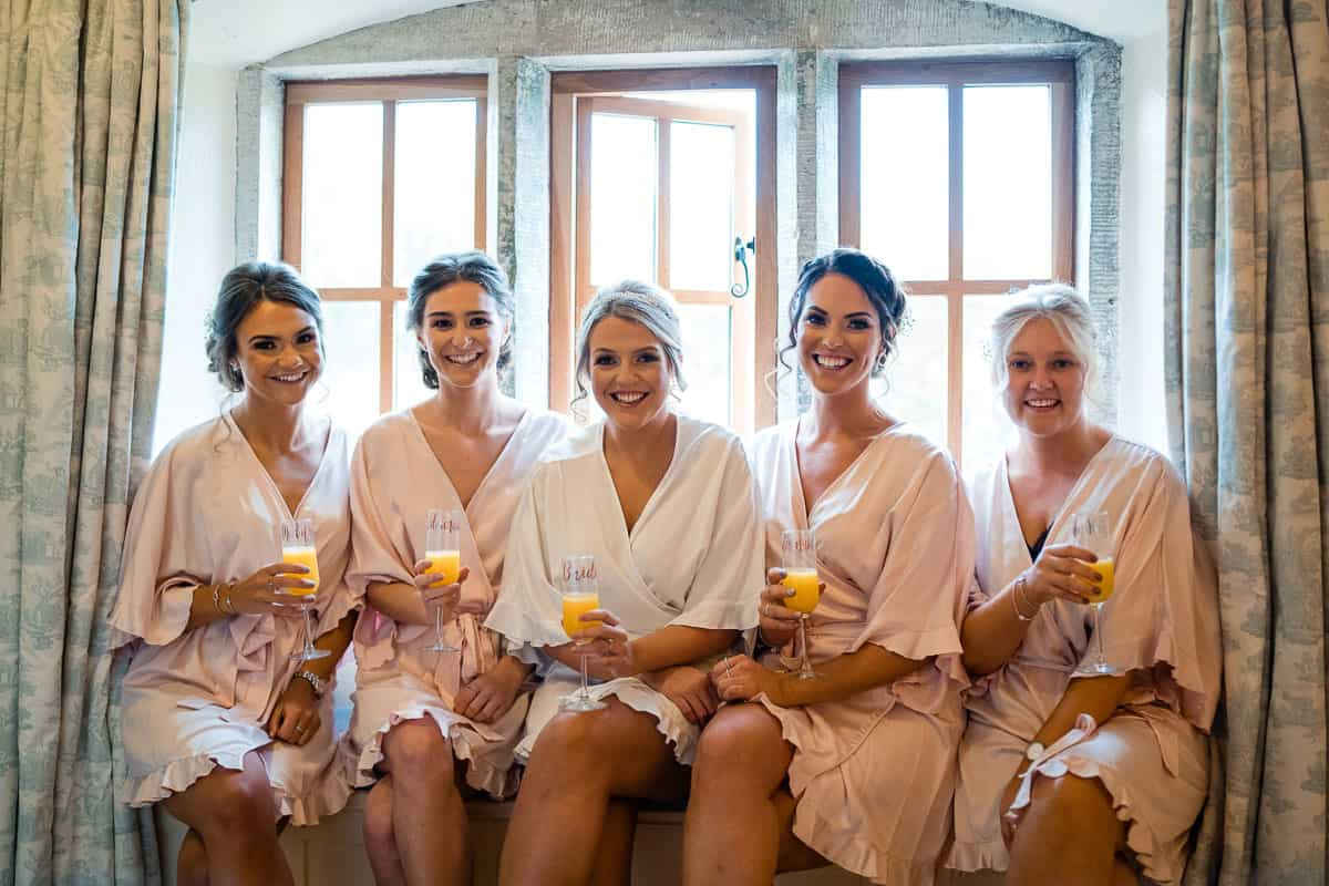 bride with her bridesmaids sat on window ledge for photograph