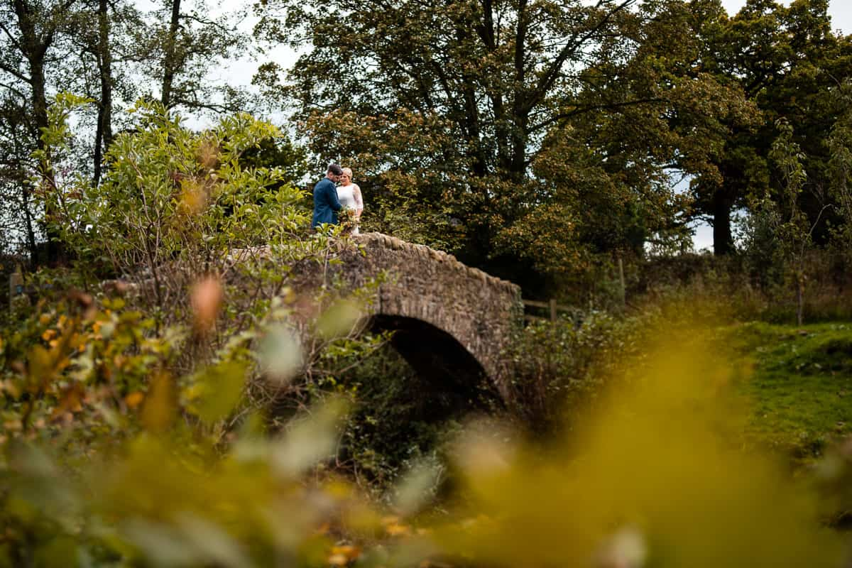 bride and groom portrait on stone bridge at the outbarn