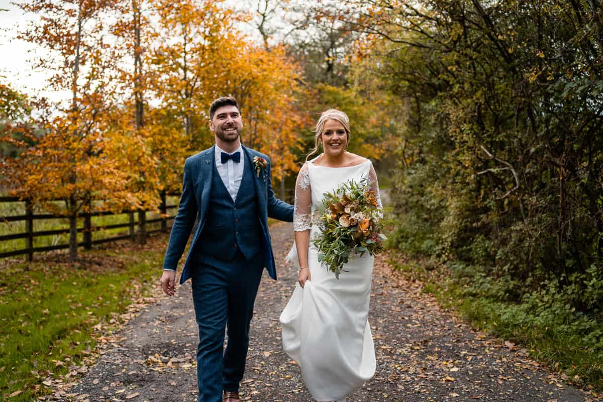 natural couple portrait walking on path with autumn colours at the outbarn