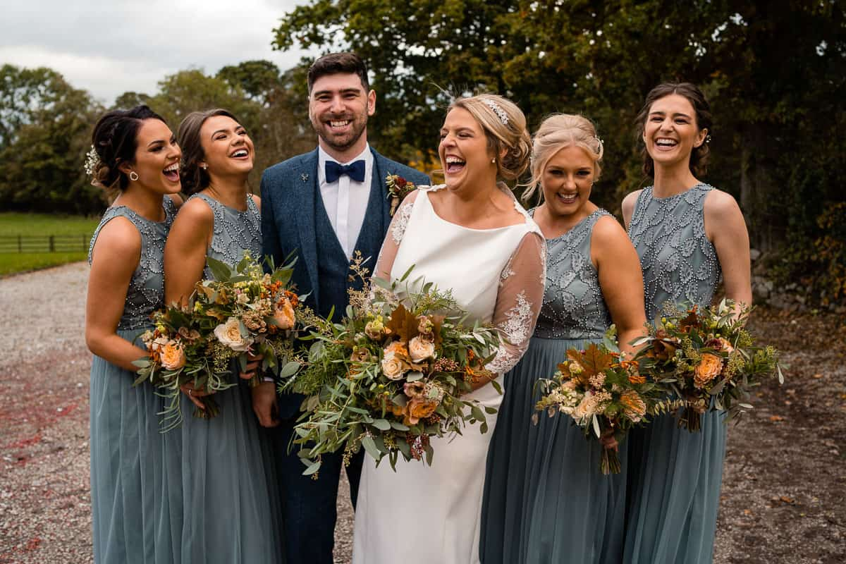 couple with bridesmaids laughing
