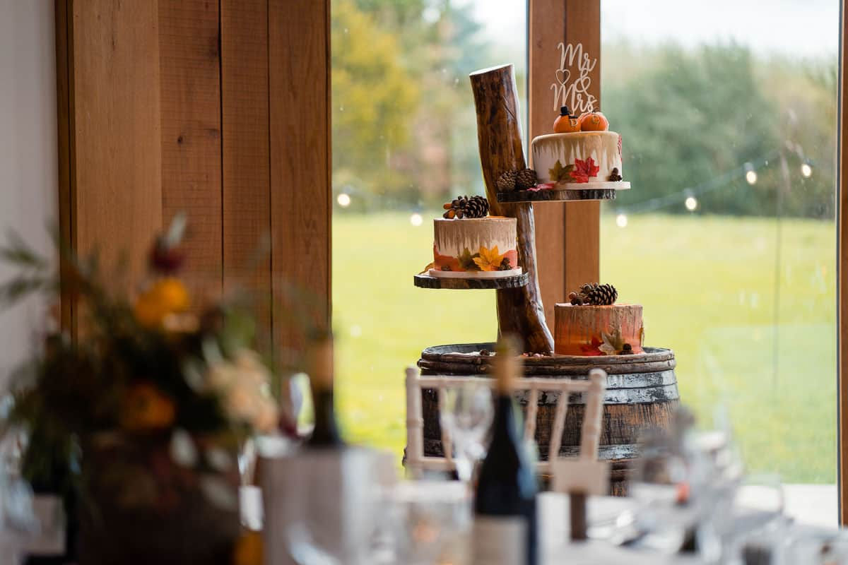 rustic cake stand with three different wedding cakes on display