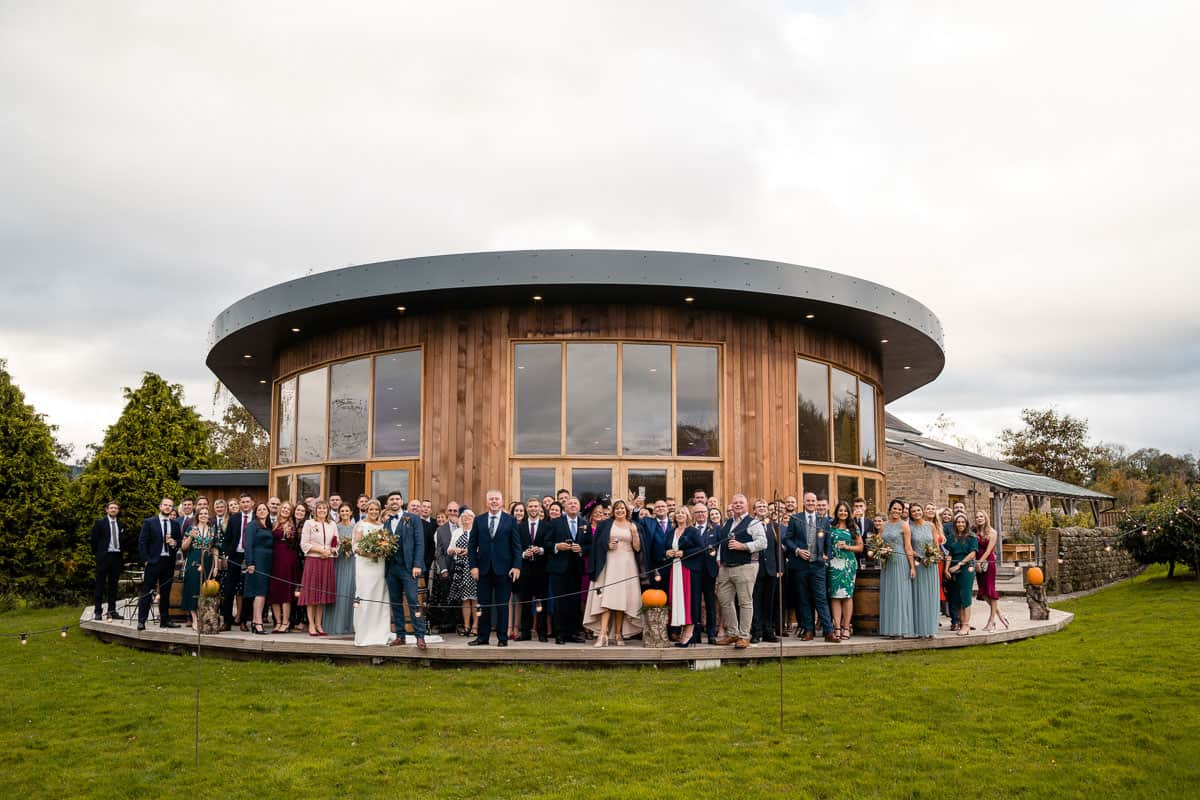 large group shot outside at the outbarn wedding venue